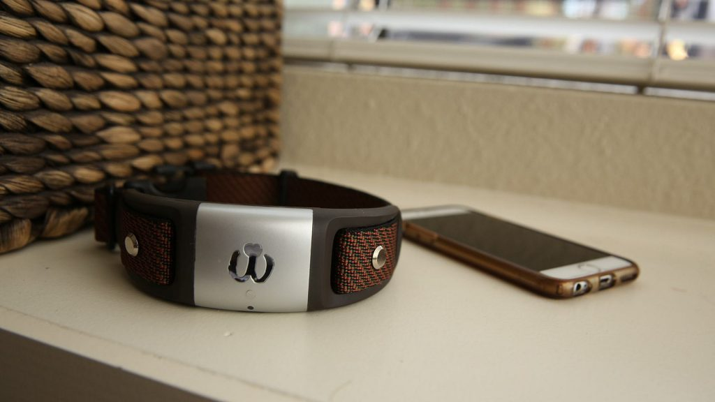 A Waggit Smart Collar sitting on the counter next to a smartphone.
